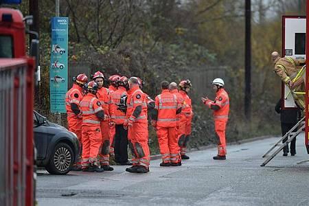 Feuerwehrleute stehen am Schauplatz nach einer große Explosion in einem Lagerhaus nahe Bristol. Foto: Ben Birchall/PA Wire/dpa