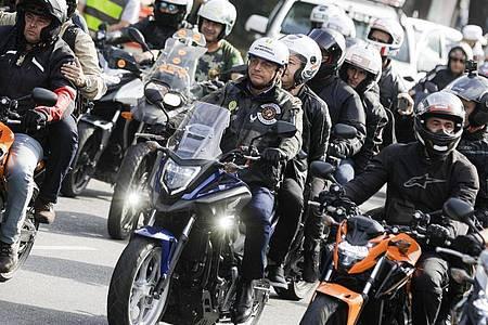 Bolsonaro in der Karawane von Motorradfahrern auf ihrem Weg durch Sao Paulo. Erst vor drei Wochen hatte Bolsonaro ohne Mund-Nasen-Schutz an einer Motorradrundfahrt durch die Millionenmetropole Rio de Janeiro teilgenommen und eine Rede vor seinen Anhängern gehalten. Foto: Marcelo Chello/AP/dpa