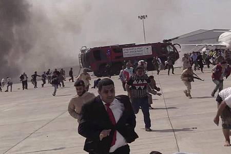Menschen rennen nach einer schweren Explosion über den Flughafen Aden. Foto: --/AP/dpa