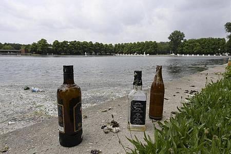 Leere Flaschen sind die letzten Überreste einer Party am Aachener Weiher in Köln. Foto: Roberto Pfeil/dpa