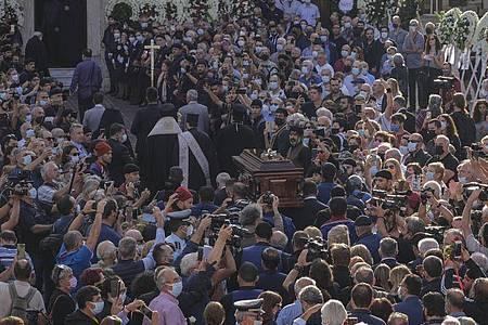 Der Sarg des griechischen Komponisten Mikis Theodorakis wird zur Trauerfeier in die Kirche getragen. Foto: Harry Nakos/AP/dpa