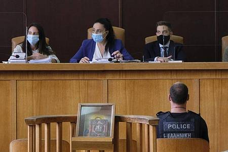 Der 28-jährige Angeklagte (vorne rechts) am ersten Verhandlungstag im Gerichtssaal. Foto: Giannis Angelakis/AP/dpa