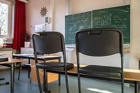 Hochgestellte Stühle in einem leeren Klassenzimmer einer Gesamtschule. Foto: Guido Kirchner/dpa