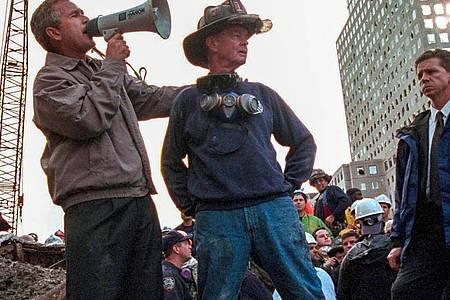US-Präsident George W. Bush spricht in den Trümmern des New Yorker World Trade Centers neben dem pensionierten New Yorker Feuerwehrmann Bob Beckwith zu den freiwilligen Helfern und Feuerwehrleuten durch ein Megafon. Foto: Eric Draper/Handout/White House/Consolidated/dpa