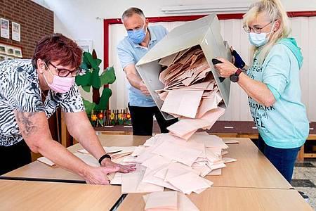 Wahlhelferinnen und ein Wahlhelfer entleeren im niedersächsischen Delmenhorst eine Wahlurne mit Stimmzetteln. Foto: Hauke-Christian Dittrich/dpa