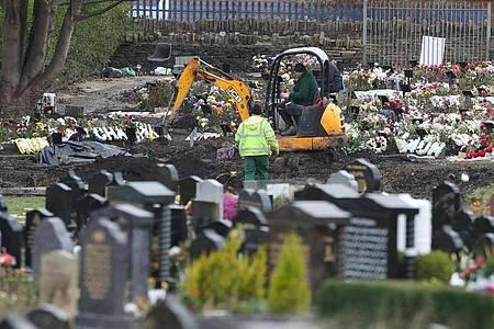 Mitarbeiter heben mit einem Bagger auf einem Friedhof in Nordengland neue Gräber aus. Foto: Danny Lawson/PA Wire/dpa