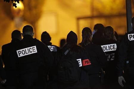 Polizisten versammeln sich vor einem Gymnasium, dem Tatort einer brutalen Messerattacke. Ein Geschichtslehrer ist ersten Erkenntnissen zufolge in der Nähe von Paris von einem Angreifer enthauptet worden. Foto: Michel Euler/AP/dpa