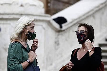 Zwei Frauen mit Masken stehen vor einer Treppe in Rom. Foto: Cecilia Fabiano/LaPresse via ZUMA Press/dpa