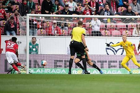 Der Mainzer Anderson Lucoqui (l) erzielt den 1:0-Führungstreffer - Fürths Torwart Sascha Burchert (2.v.r.) kann das Gegentor nicht mehr verhindern. Foto: Sebastian Gollnow/dpa