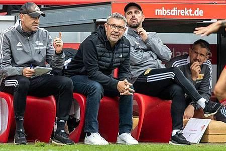 Unions Co-Trainer Markus Hoffmann (l-r), Trainer Urs Fischer und Co-Trainer Sebastian Bönig sitzen auf Bank. Foto: Andreas Gora/dpa