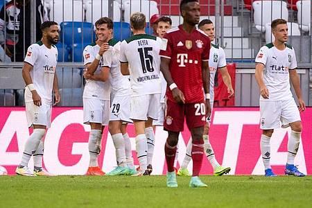 Die Gladbacher Spieler (hinten) feiern das Tor zum 1:0 gegen Bayern München. Foto: Sven Hoppe/dpa