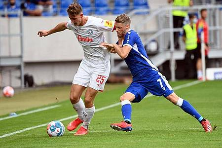 Der Karlsruher Marc Lorenz (r) und der Kieler Phil Yannik Neumann kämpfen um den Ball. Foto: Uli Deck/dpa