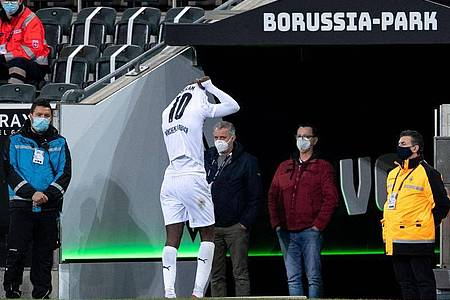 Mönchengladbachs Marcus Thuram verlässt nach seiner Spuckattacke das Feld. Foto: Marius Becker/dpa-Pool/dpa