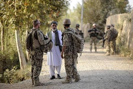 Ein Bundeswehrsoldat (l) und ein Dolmetscher (r) sprechen nahe Kundus im Distrikt von Char Darreh mit einem Mann. Foto: Maurizio Gambarini/dpa