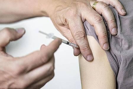 Ein Kinder- und Jugendarzt impft eine junge Frau mit dem Corona-Impfstoff Comirnaty von Biontech/Pfizer. Foto: Fabian Sommer/dpa