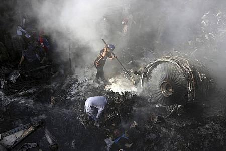 Helfer und Einsatzkräfte suchen nach dem Absturz einer Maschine der Fluggesellschaft Pakistan International Airlines (PIA) in Karatchi nach Überlebenden. Foto: Fareed Khan/AP/dpa/Archiv