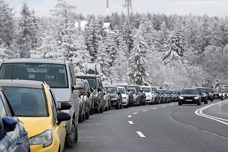 Fahrzeuge stehen auf Behelfsparkplätzen an der Bundesstraße 242 zwischen Braunlage und Torfhaus im Harz. Foto: Swen Pförtner/dpa
