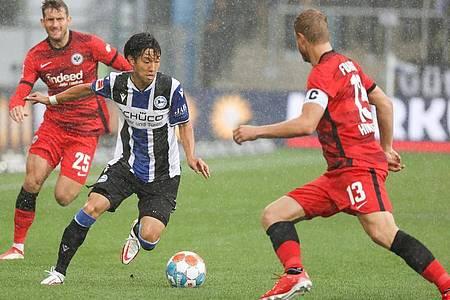 Bielefelds Masaya Okugawa (M) zieht im Dribbling gegen Frankfurts Martin Hinteregger (r) ins Eins gegen Eins. Foto: Friso Gentsch/dpa