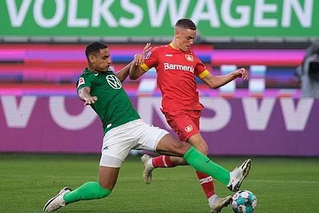 Wolfsburgs Neuzugang Maxence Lacroix (l) setzt gegen Leverkusens Talent Florian Wirtz zur Grätsche an. Foto: Peter Steffen/dpa