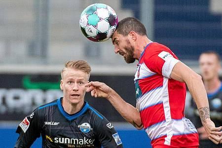 Norman Theuerkauf (r) vom FC Heidenheim und Paderborns Chris Führich liefern sich einen Zweikampf um den Ball. Foto: Stefan Puchner/dpa