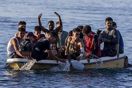 Migranten kommen in der spanischen Enklave Ceuta, nahe der Grenze zwischen Marokko und Spanien, an. Foto: Bernat Armangue/AP/dpa