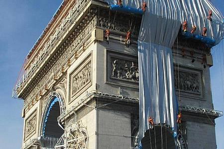Gebäudekletterer haben mit der Verhüllung des Triumphbogens (Arc de Triomphe) begonnen. Foto: Sabine Glaubitz/dpa