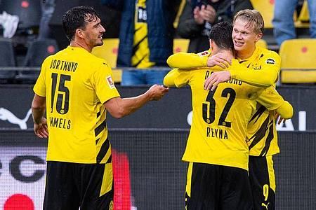 Mats Hummels (l) feiert mit dem Giovanni Reyna (32) umarmenden Erling Haaland einen Treffer im Spiel gegen den SC Freiburg. Foto: Guido Kirchner/dpa