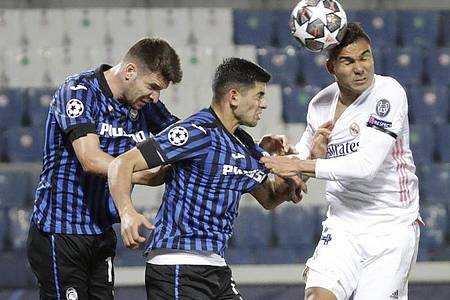 Real Madrids Casemiro (r) köpft den Ball an Atalantas Cristian Romero (M) und Atalantas Berat Djimsiti vorbei. Foto: Luca Bruno/AP/dpa