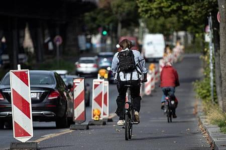 Radfahrer sind auf dem Pop-up-Radweg am Halleschen Ufer unterwegs, während ein Pkw verbotswidrig auf der Fahrbahn daneben parkt. Foto: Paul Zinken/dpa-Zentralbild/dpa