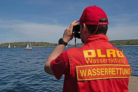 Ein Mitglied der Deutschen Lebensrettungs-Gesellschaft (DLRG) beobachtet die Boote auf dem Wannsee. Foto: Paul Zinken/dpa