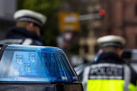Zwei Polizeibeamte stehen zwischen zwei Einsatzfahrzeugen der Polizei. Über Pfingsten gibt es eine Vielzahl von Demonstrationen in Berlin. Zwei große Veranstaltungen wurden von der Polizei verboten - nun hat das Oberverwaltungsgericht dazu entschieden. Foto: Philipp von Ditfurth/dpa