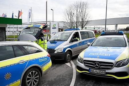 Fahrzeuge der Polizei stehen vor einem Werk eines Getränkeherstellers. Dort hatte eine Serie explosiver Postsendungen begonnen. Foto: Rene Priebe/dpa