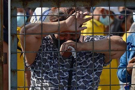 Eine Frau weint vor der Haftanstalt, in der es zu gewalttätigen Auseinandersetzungen zwischen verfeindeten Banden gekommen ist. Die Zahl der Todesopfer ist auf über 100 gestiegen. Foto: Marcos Pin/dpa