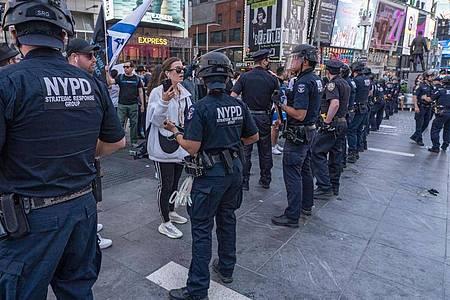 Polizisten stellen sich bei einem Zusammenstoß zwischen Unterstützern der Palästinenser und Unterstützern von Israel auf dem Times Square. Foto: Ron Adar/SOPA Images via ZUMA Wire/dpa