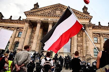 Teilnehmer einer Kundgebung gegen die Corona-Maßnahmen stehen vor dem Reichstag, ein Teilnehmer hält eine Reichsflagge. (zu dpa «Innenminister: Bundesweiter Erlass gegen Reichskriegsflaggen steht»). Foto: Fabian Sommer/dpa