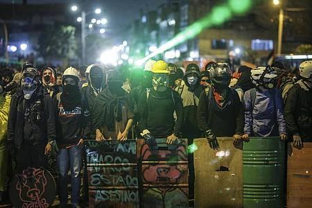 Demonstranten stehen bei einem Protest an einer Kreuzung mit Schildern und Laserpointern. Foto: Ivan Valencia/AP/dpa