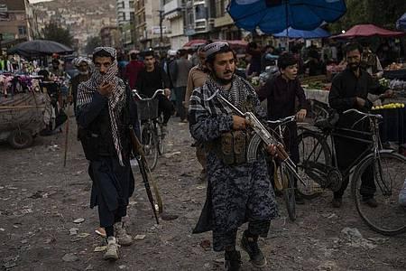 Taliban-Kämpfer patrouillieren auf einem Markt in der Altstadt. Foto: Bernat Armangue/AP/dpa