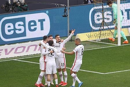 Frankfurts Stürmer André Silva (33) feiert die 1:0-Führung in Dortmund mit den Mannschaftskollegen. Foto: Lars Baron/Pool Getty/dpa
