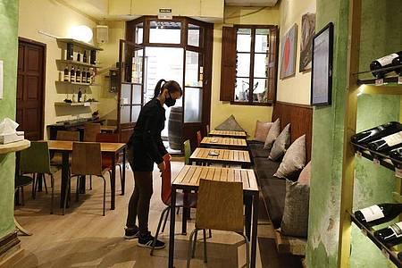 Eine Kellnerin mit Maske bereitet in Palma den Innenraum eines Restaurants für das Tagesgeschehen vor. Foto: Clara Margais/dpa