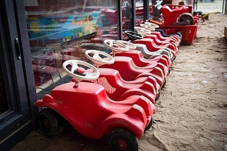 Mehrere Bobbycars stehen auf dem Spielplatz eines Kindergartens. Foto: Christian Charisius/dpa/Symbolbild