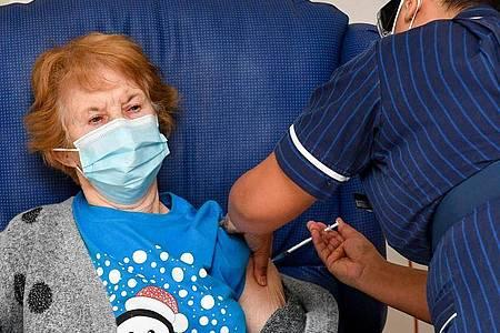 Die 90-jährige Margaret Keenan (l) bekommt im Universitätskrankenhaus Coventry von der Krankenschwester May Parsons den Pfizer/BioNtech-Impfstoff gegen das Coronavirus. Foto: Jacob King/PA Wire/dpa