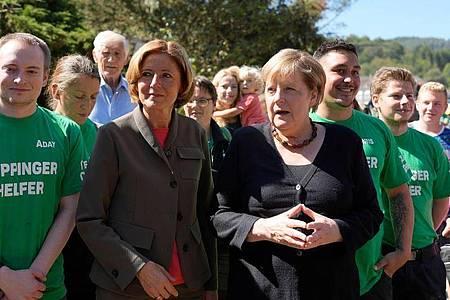 Bundeskanzlerin Angela Merkel (CDU, r.) steht mit freiwilligen Helfern neben der rheinland-pfälzischen Ministerpräsidentin Malu Dreyer bei ihrem Besuch im hochwassergeschädigten Altenahr. Foto: Markus Schreiber/AP-Pool/dpa