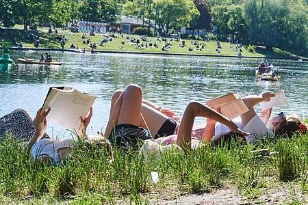 Drei Frauen liegen auf der Wiese am Landwehrkanal in Berlin und lesen Bücher. Foto: Annette Riedl/dpa