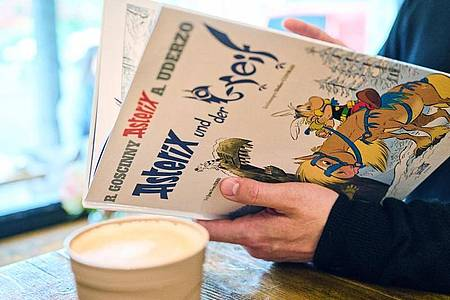 """Ein Mann schaut in den neuen Asterix-Band """"Asterix und der Greif"""". Foto: Annette Riedl/dpa"""