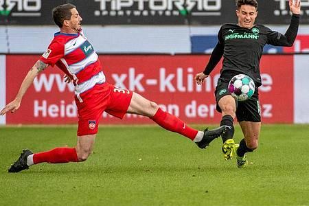 Heidenheims Norman Theuerkauf (l) und Fürths Marco Meyerhöfer grätschen beide zum Ball. Foto: Stefan Puchner/dpa
