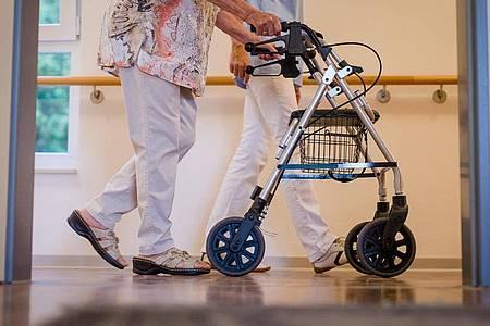 Eine Pflegekraft geht in einem Pflegeheim mit einer älteren Dame über einen Korridor. Alten- und Pflegeheime sollen ab dem 15. Oktober flächendeckend Coronatests durchführen. Foto: Christoph Schmidt/dpa