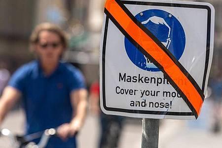Ein mit orangen Klebeband durchgestrichenes Schild steht in der Münchner Innenstadt am Straßenrand. Die weitgehende Aufhebung der Maskenpflicht in Dänemark befeuert auch in Deutschland die Diskussion über den Sinn des Mund-Nasen-Schutzes. Foto: Peter Kneffel/dpa