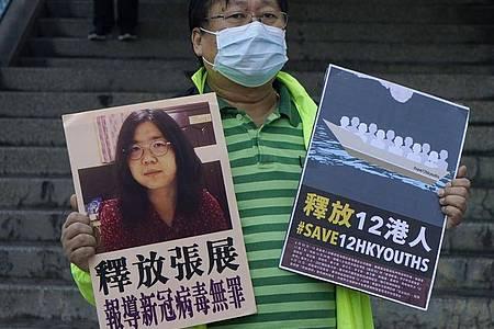 Ein pro-demokratischer Aktivist zeigt zwei Plakate vor dem Verbindungsbüro der chinesischen Zentralregierung. Auf einem Plakat ist ein Foto der chinesischen Journalistin Zhang Zhan zu sehen. Foto: Kin Cheung/AP/dpa