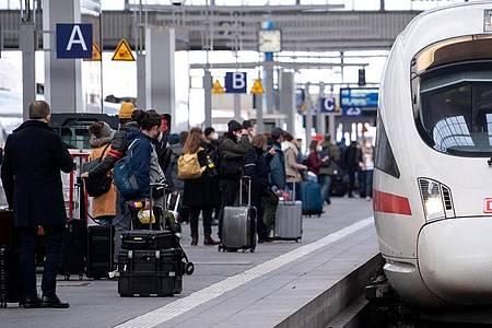 Reisende neben einem ICE am Münchener Hauptbahnhof. Foto: Sven Hoppe/dpa