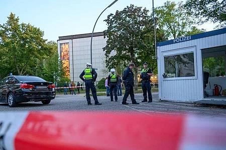Polizeibeamte und Zivilisten stehen im abgesperrten Bereich vor der Synagoge in Hamburg-Harvestehude. Foto: Jonas Walzberg/dpa